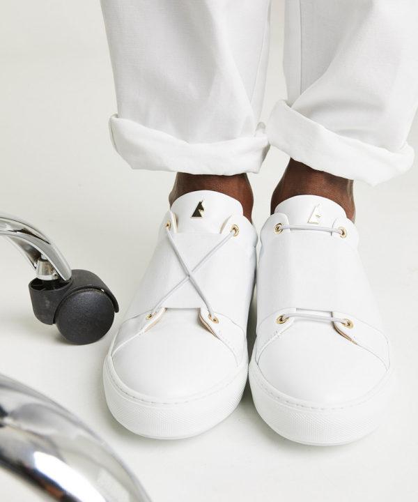 ces sneakers monochromatiques jouent le jeu du contraste avec leurs lacets colorés.